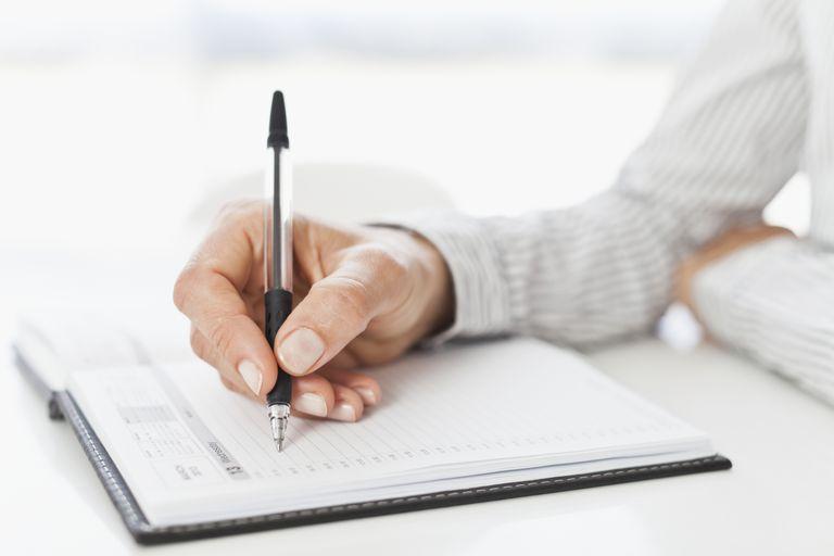 woman writing in calendar