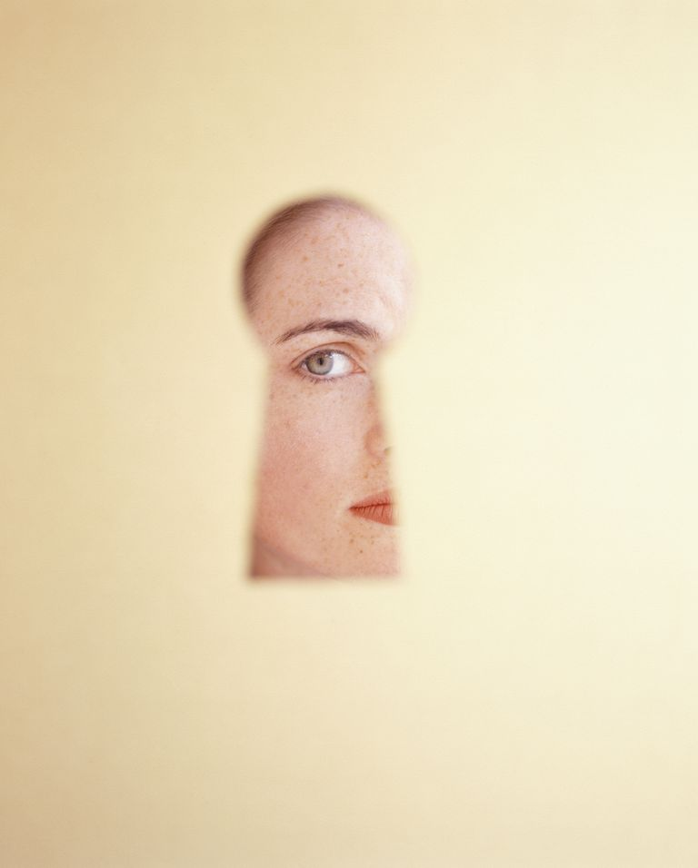 Woman looking through keyhole