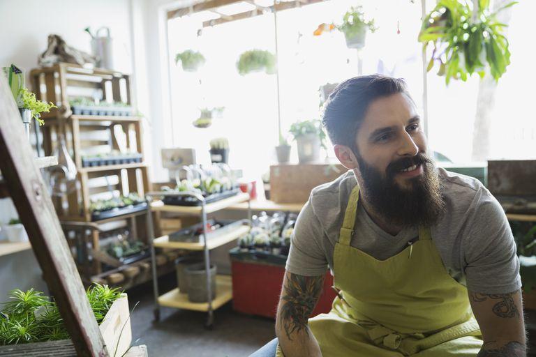 A tattooed man sits in a terrarium shop.