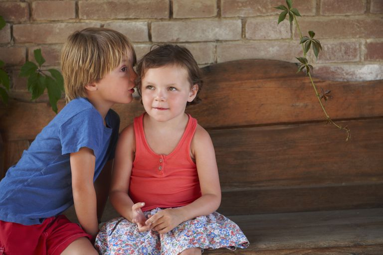 Boy whispering into girl's ear