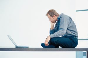Businessman thinking while sitting and looking at a computer