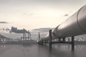 Oil pipeline in industrial district with factories at dusk