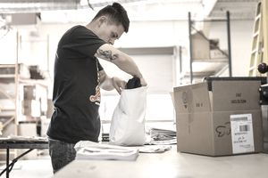 Worker packing garment in screen print workshop