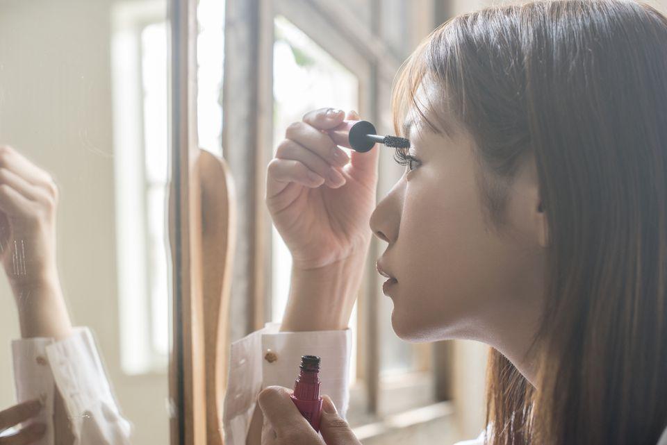 Woman applying a mascara on her eye lush.