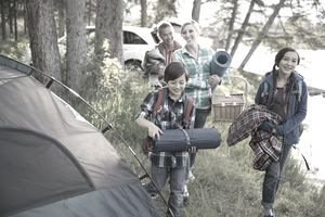 Family carrying gear at campsite