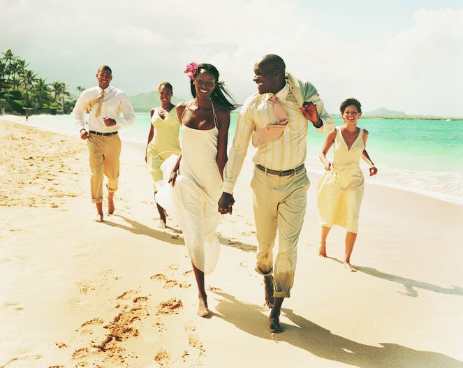 Newlywed Couple Walk on a Beach Hand-in-Hand, Accompanied by Bridesmaids and Best Man