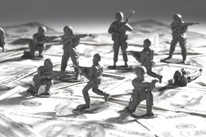 Close-up of plastic toys fighting on paper currency