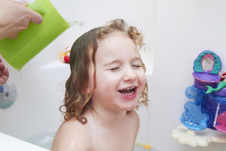 A three year old girl in the bath tub.