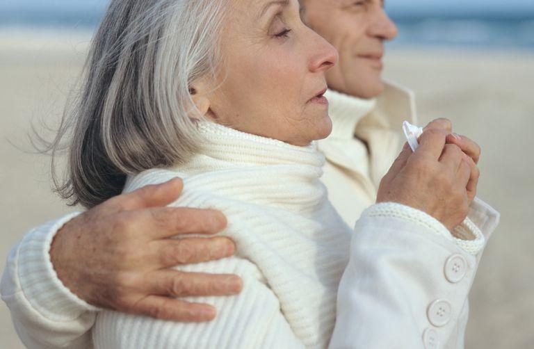 Senior woman sneezing and walking with senior man