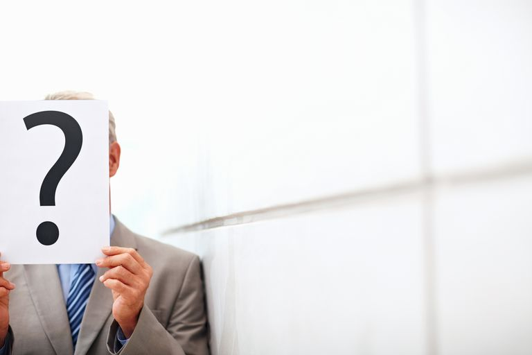 man in suit holding paper with question mark
