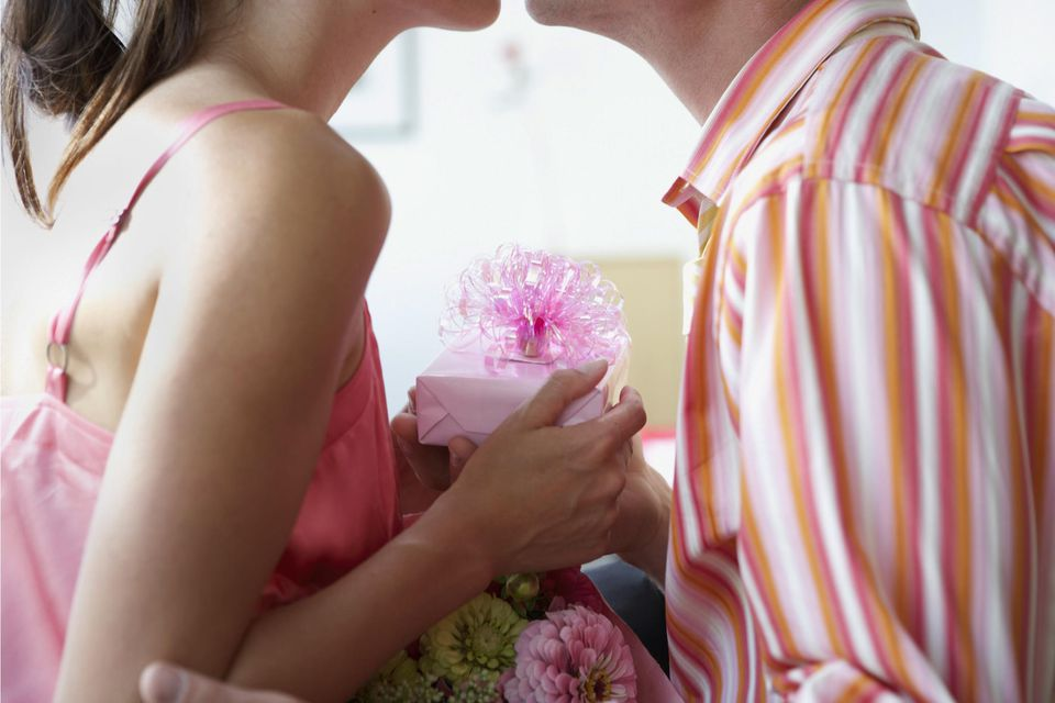 Man and woman kissing, woman holding gift, side view