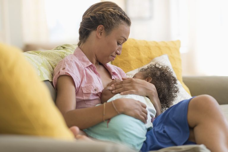 Mixed race mother nursing daughter in living room