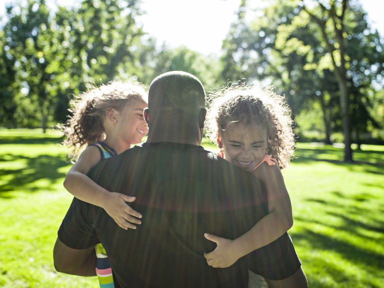 Father playing with twin daughters in park