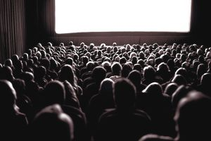 Crowd watching movie in theatre, rear view