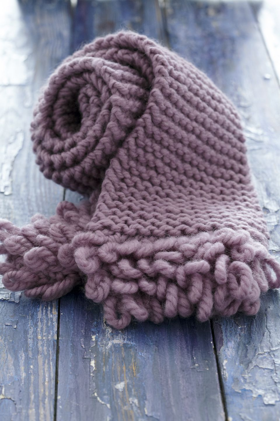 Make a scarf with some of the bulky yarn in your stash pink knitted scarf with loop fringe on wood background bankloansurffo Choice Image