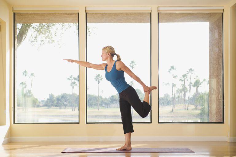 Photo of a woman performing yoga balance exercises.