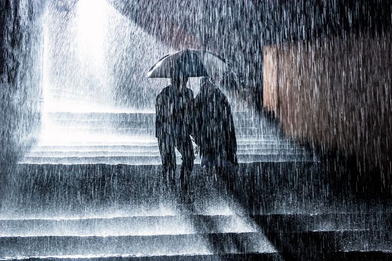 Two people under an umbrella during a rainstorm.