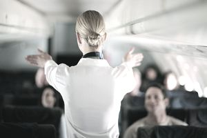 A flight attendant explains safety procedures to passengers