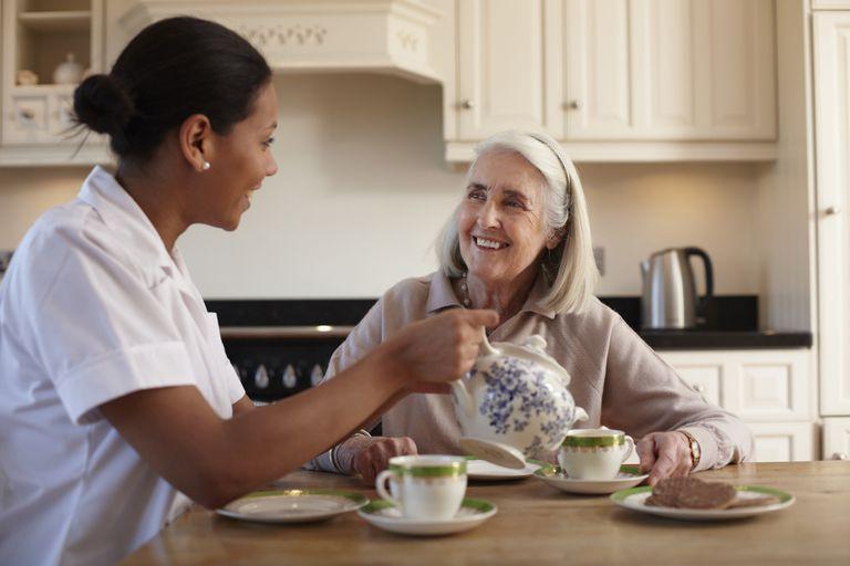 Home care worker serving elderly woman tea.