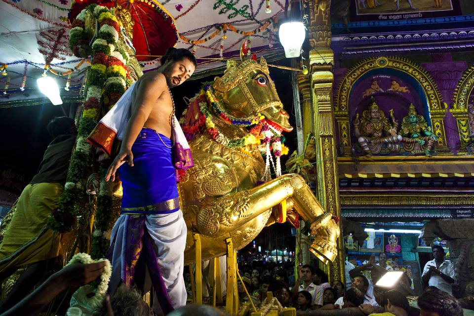 Priest with golden horse statue in temple festival procession entering Sri Meenakshi Temple.