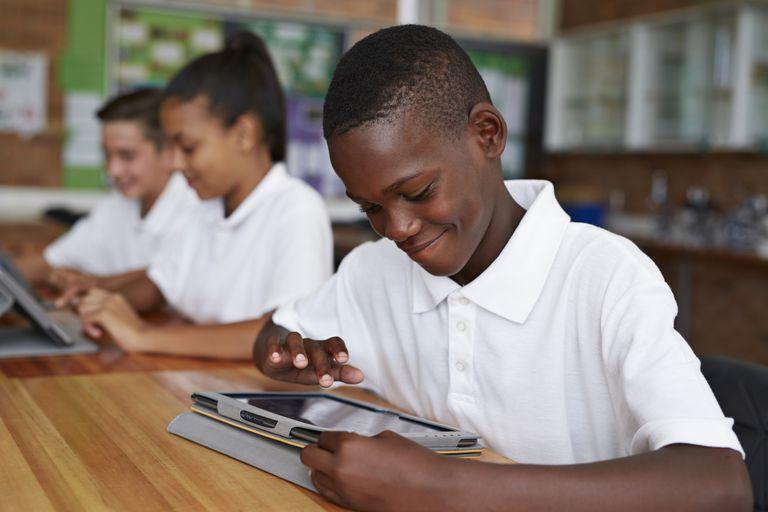 Happy school kid scrolling on tablet