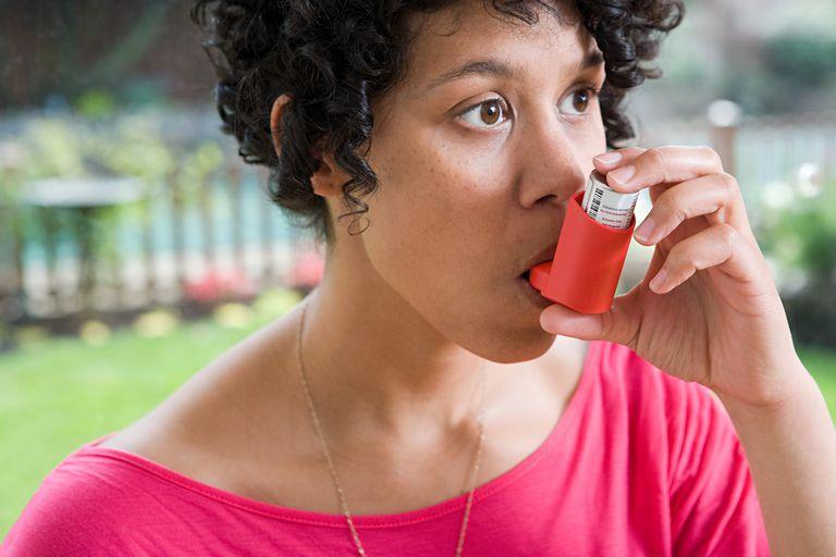 Woman taking asthma inhaler