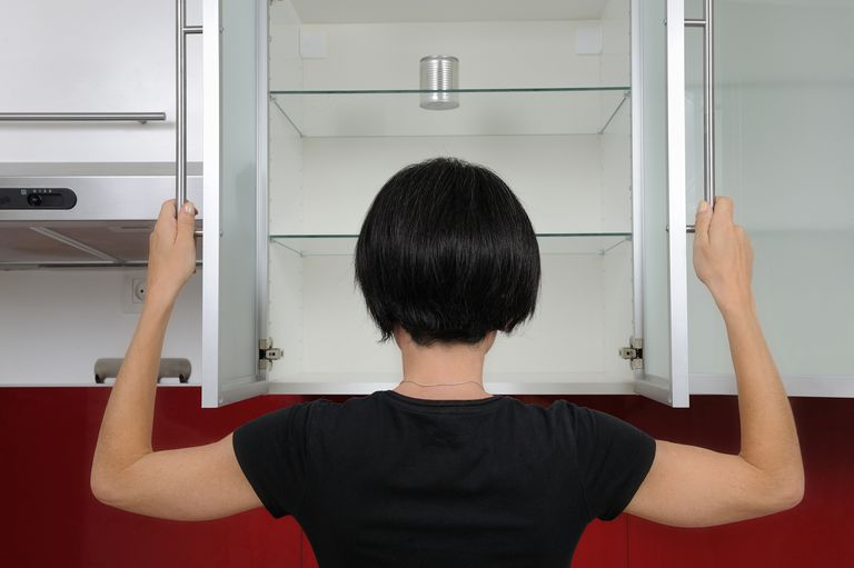A woman looks inside an empty cupboard.