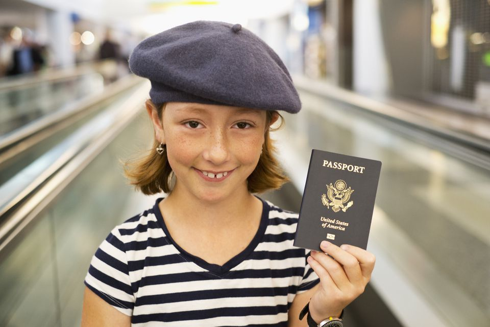 Young girl holding her passport at the airport