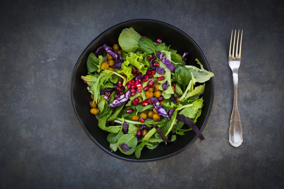 Bowl of mixed leaf salad with pomegranate seed, red cabbage and roasted curcuma chick peas