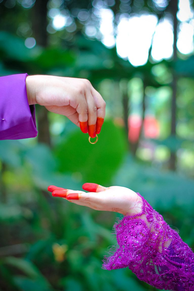 Cropped Image Of Groom Giving Ring To Bride At Forest