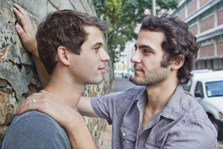 Gay male couple meeting on street
