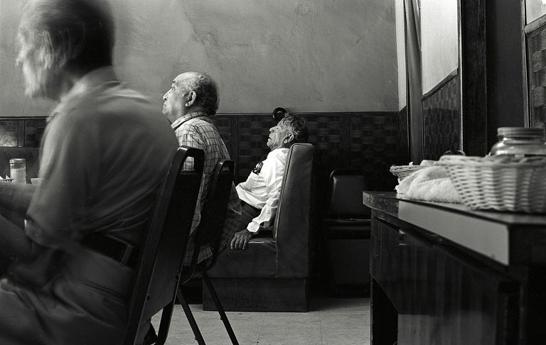 An elderly man sleeps in a cafe, illustrating how disengagement theory describes the process of aging.