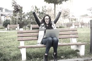 Happy young woman, sitting on park bench while winning a bid in an online auction.