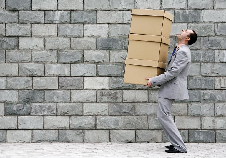 Businessman carrying a stack of boxes