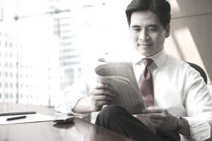 Chinese business man reading newspaper