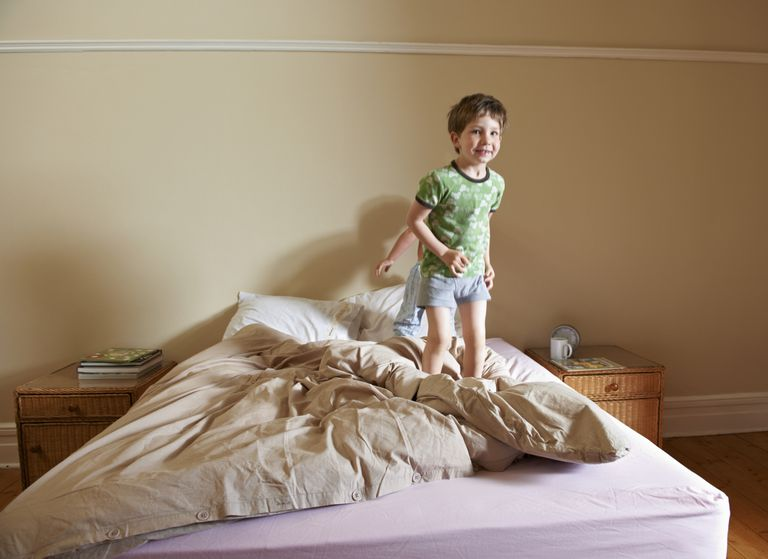 Boys jumping on parents bed