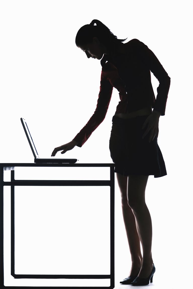 Silhouette of businesswoman using laptop