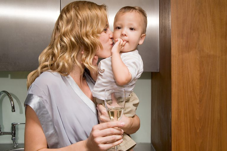 A woman with a baby and a glass of wine