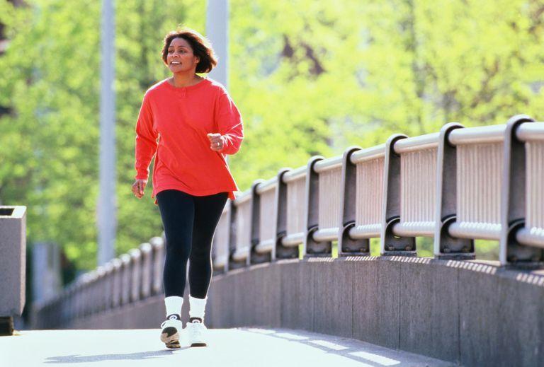 Solo woman walking across bridge