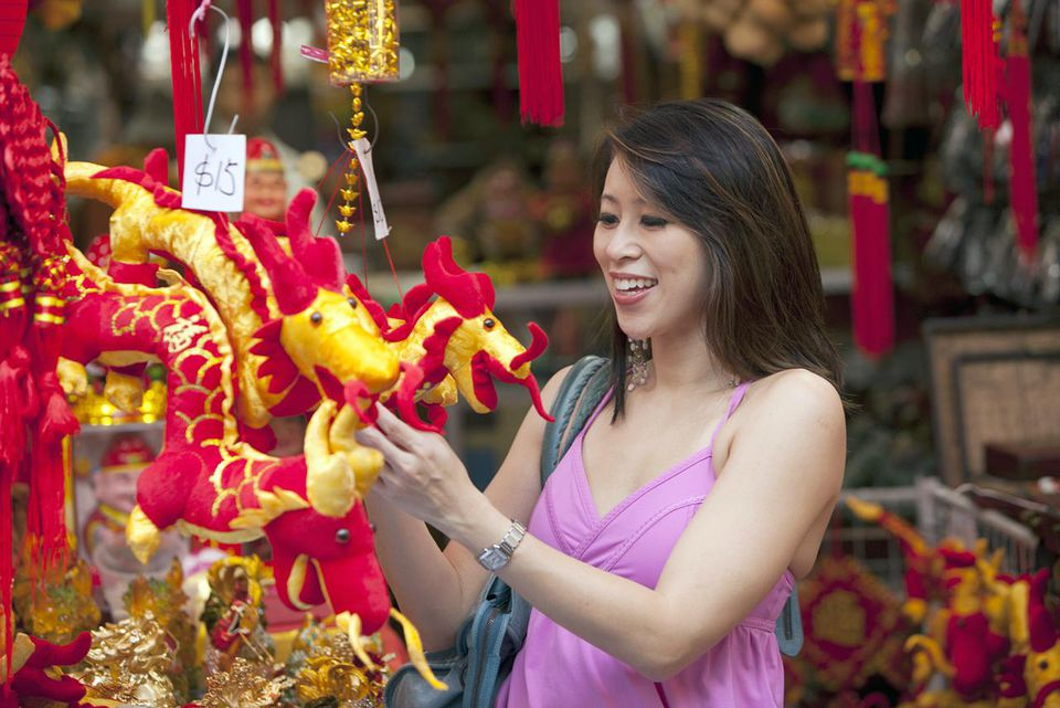 Chinese woman looking at dragon, shopping in chinatown
