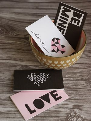 Four pink, black, and white Valentine cards