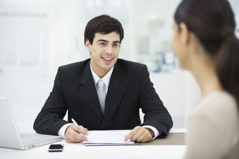Businessman sitting at desk, talking with woman and smiling