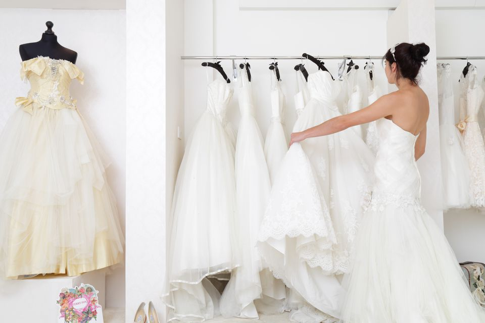 Woman in a bridal shop looking at wedding dresses
