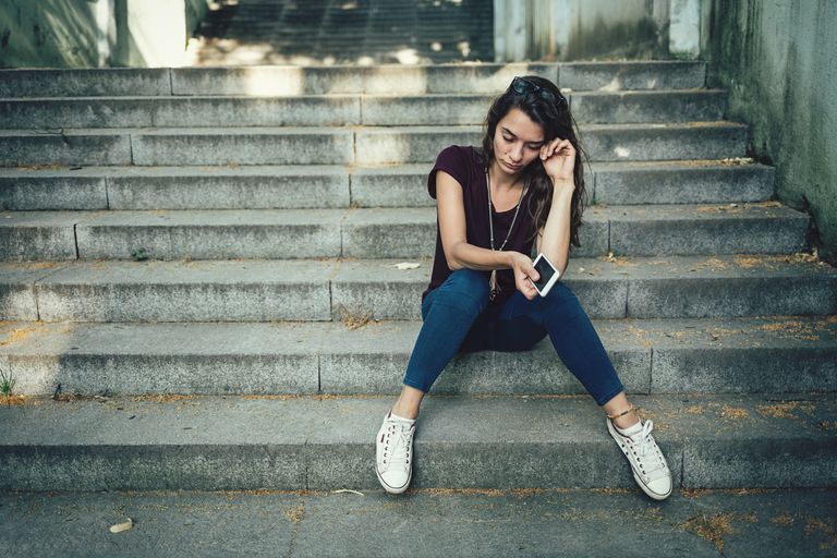 Upset teen sitting on stairs