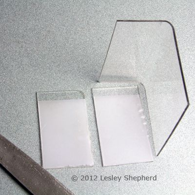 Round the top corners of the dollhouse display case using a file and sandpaper.
