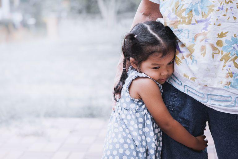 Sad asian little girl hugging her mother leg