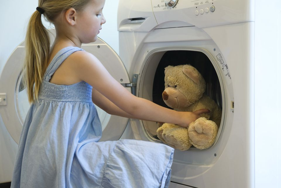 Little girl taking teddy bear out of dryer