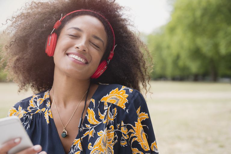 Enthusiastic woman listening to music with headphones and mp3 player in park