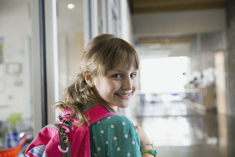 Confident girl enters a school building.