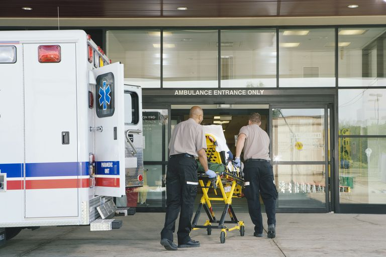Paramedics taking patient on stretcher from ambulance to hospital